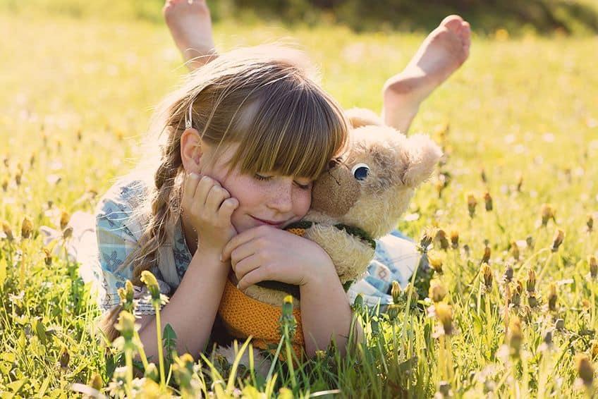 little girl hugging a stuffed bunny in a field of flowers