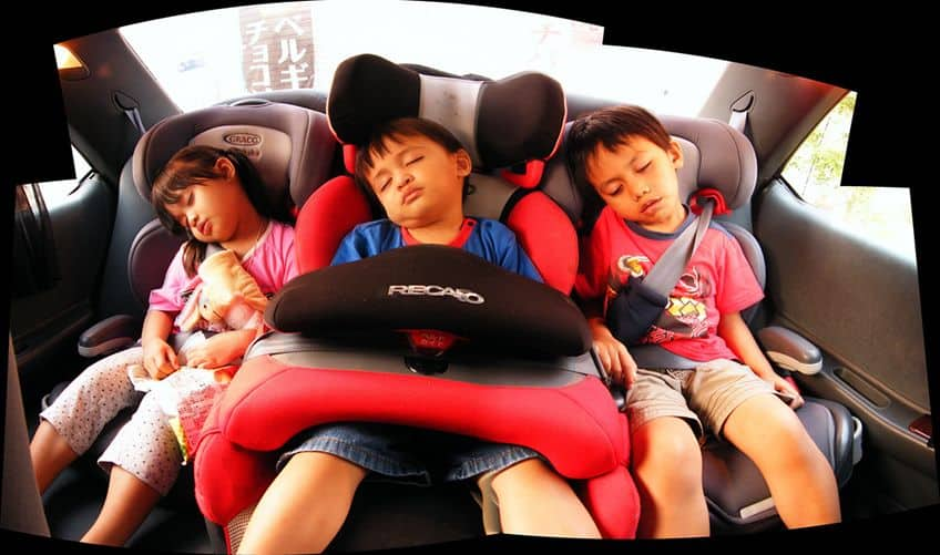 3 kids asleep in the back of the car