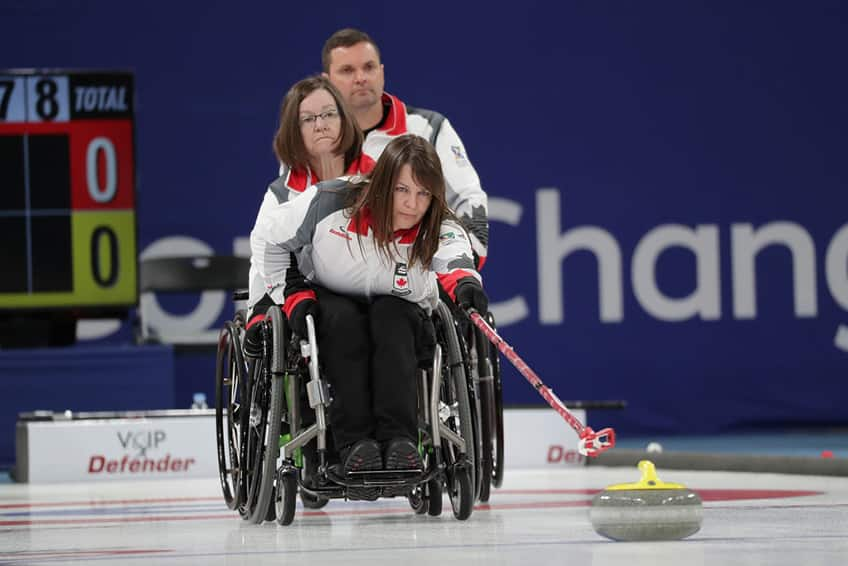 Ina Forrest throws a rock from her wheelchair
