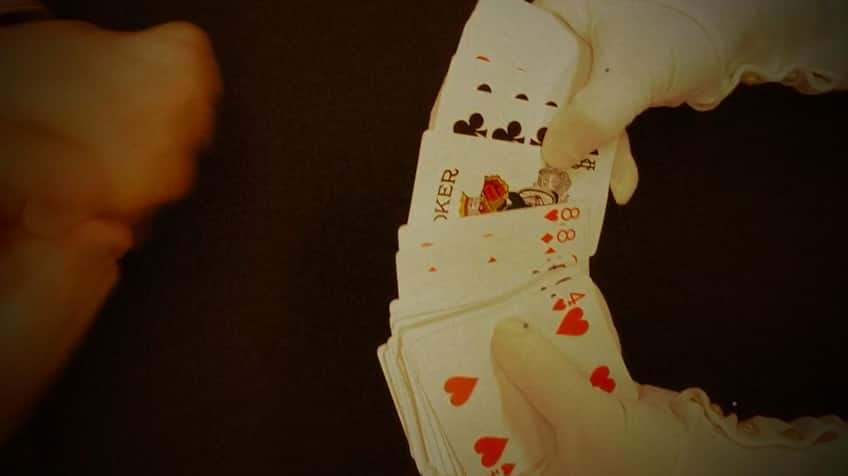 Magician has cards splayed to find Joker in middle of deck.