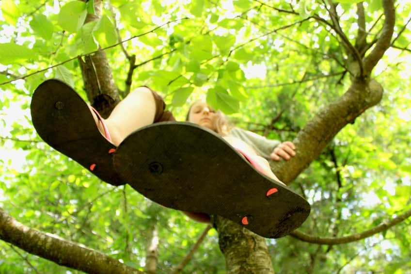 Looking up at a child climbing a tree.