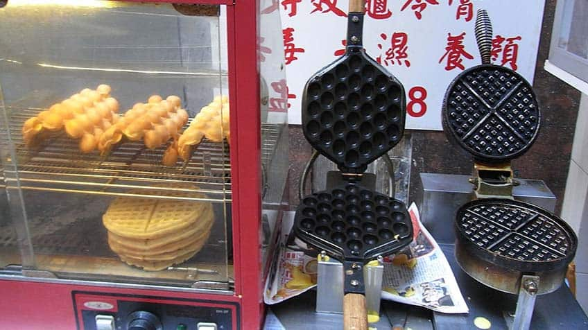 Bubble waffles in warming oven; waffle irons on display