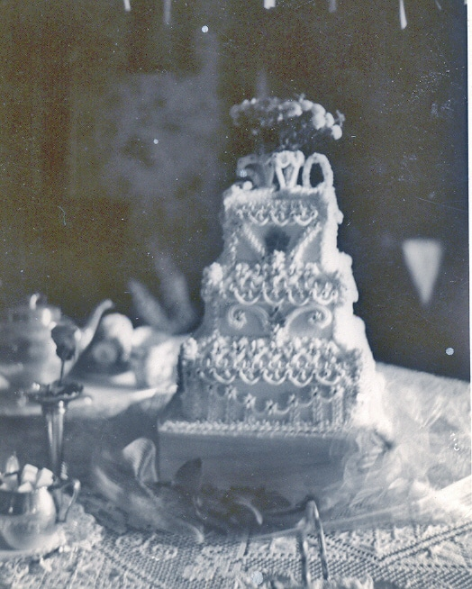 Black and white picture of a three-tiered wedding cake.