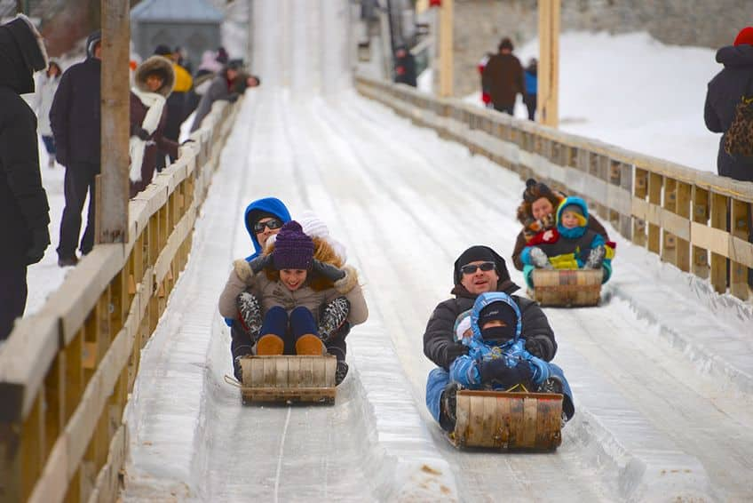 people tobogganing down an ice hill