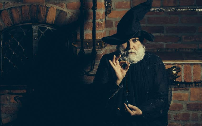 a man dressed up as a warlock in front of a fireplace