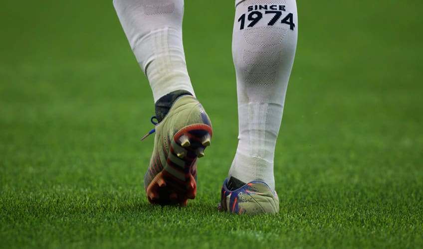 A fine rubber material from the new artificial turf coats the shoes of a player during a game in Vancouver, BC.