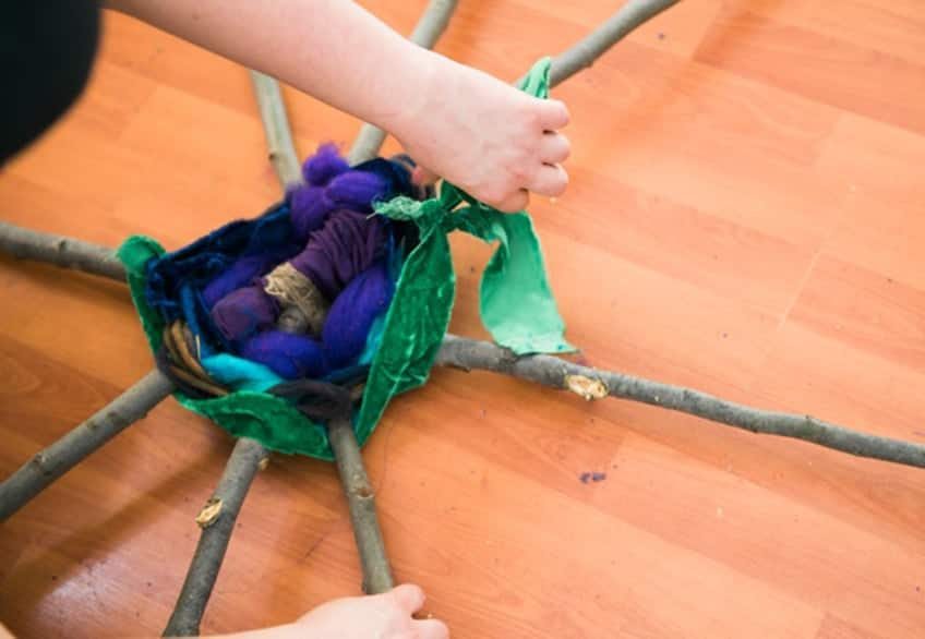 wrapping fabric around the twigs
