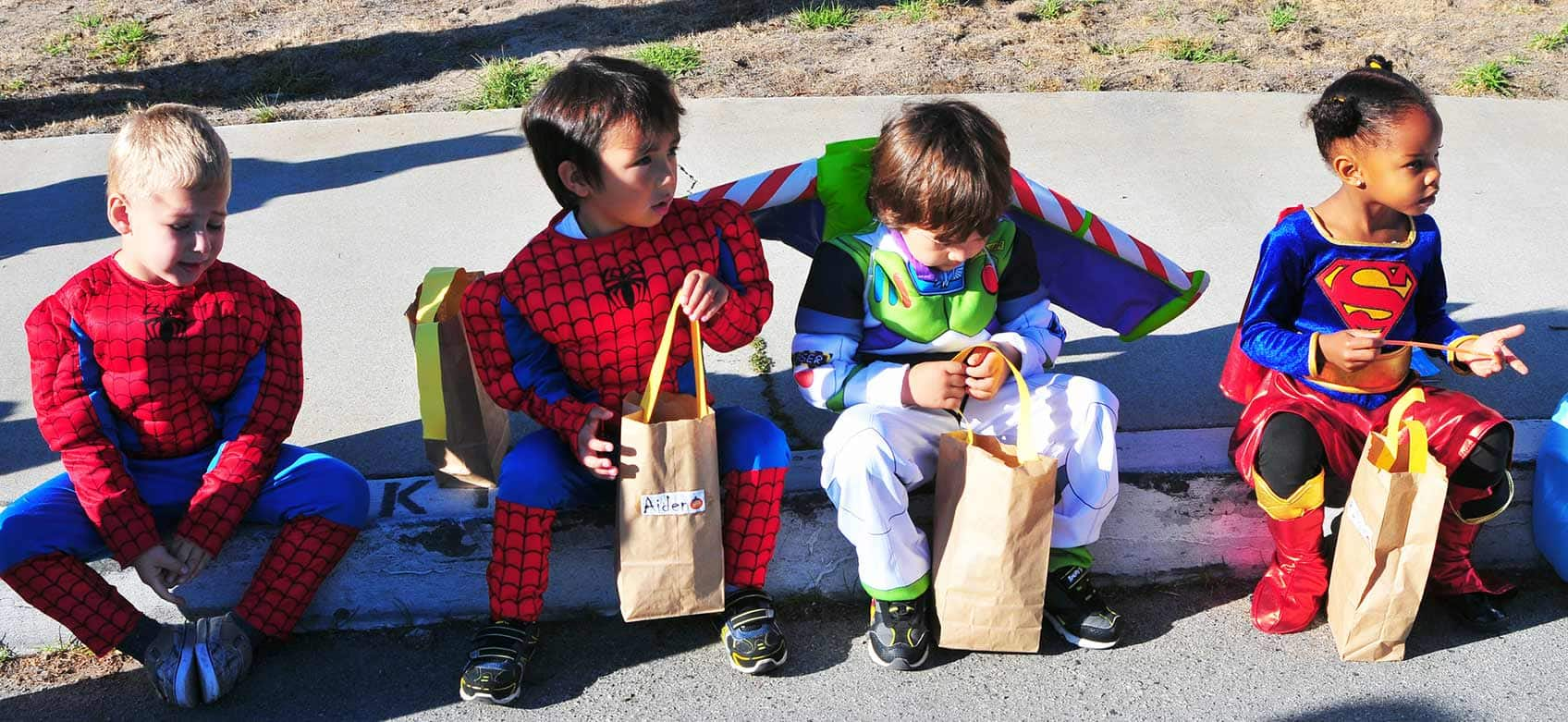 kids dressed up as superheroes to trick or treat