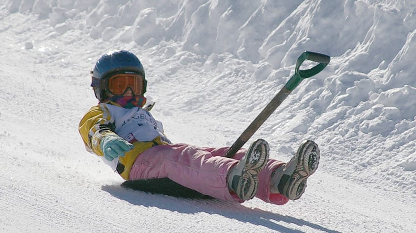 A little kid racing down a hill while sitting on a shovel.