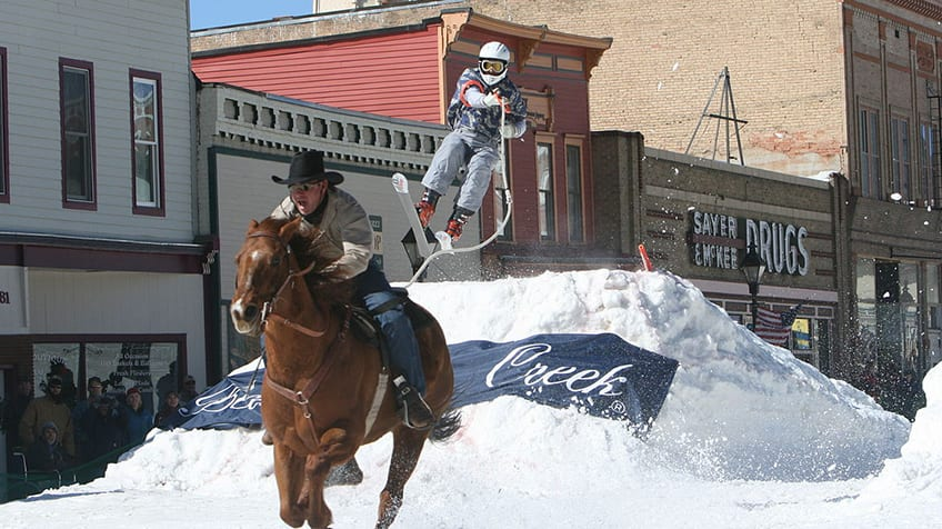 A man skijoring - a sport where he's pulled behind a horse while on skis.