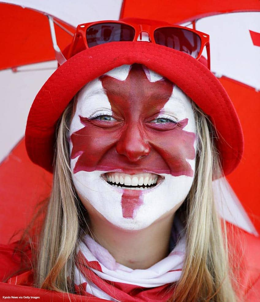 A Canadian fan with their face painted as a maple leaf