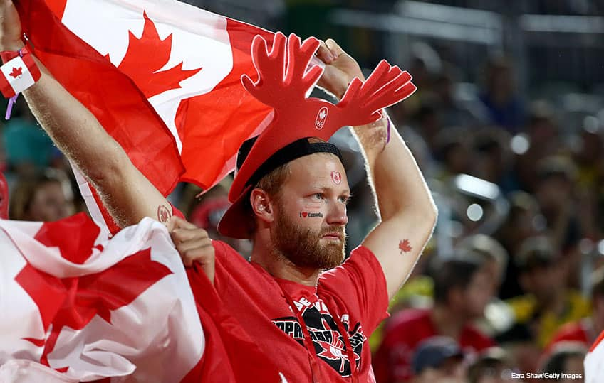 a Canadian fan wearing red antlers and holding a Canadian flag