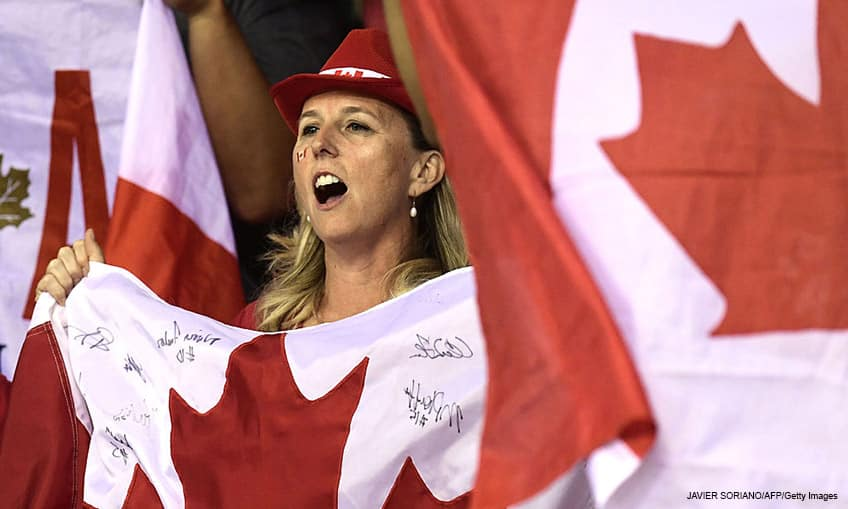 A Canadian fan celebrates after a basketball match with a flag