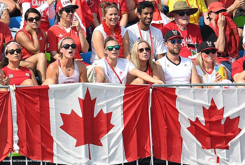 Canadian fans watch the men's field hockey match behind a wall of flags