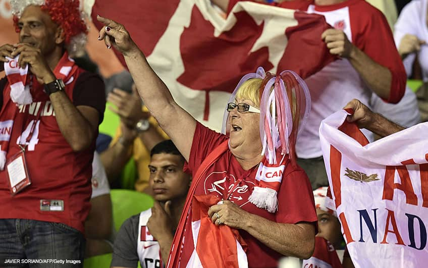 A Canadian fan with multicolour hair celebrates during the basketball match