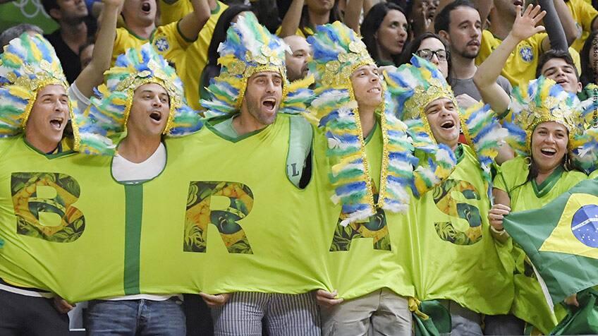 Brazil fans cheer wearing colourful head dress.