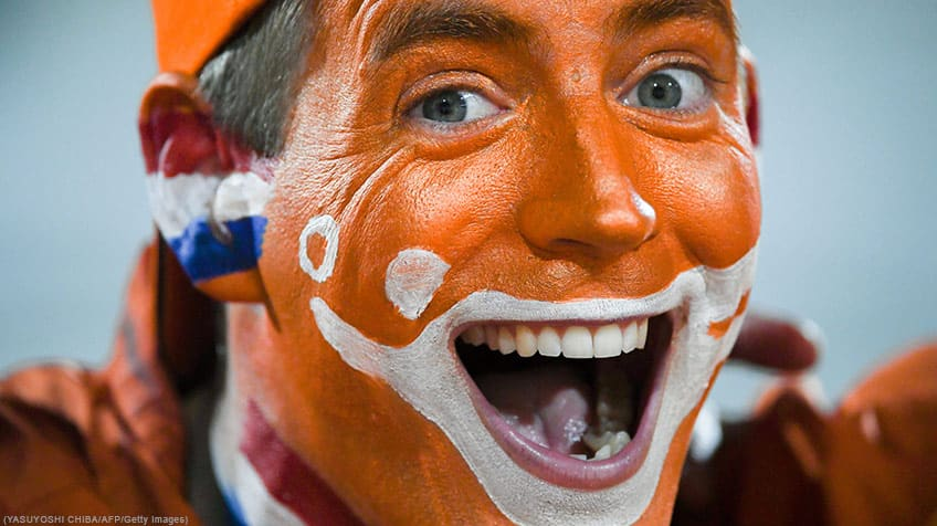 Dutch fan wearing colourful face paint.