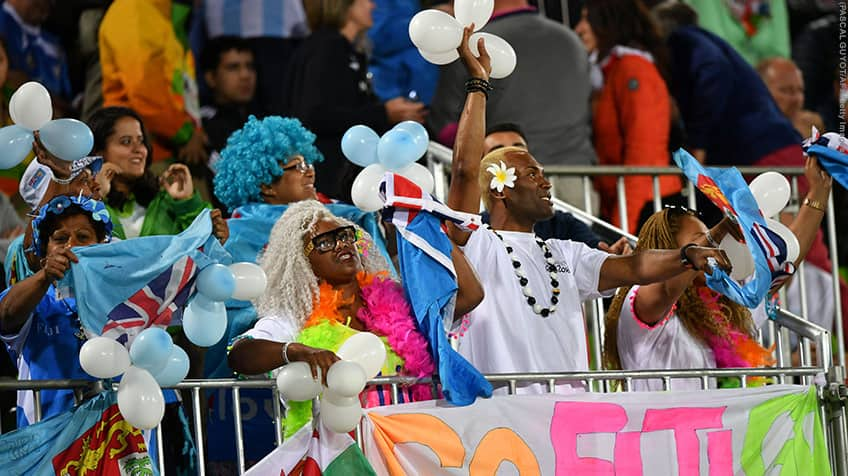 Blue haired fans cheering on Fiji with flags.