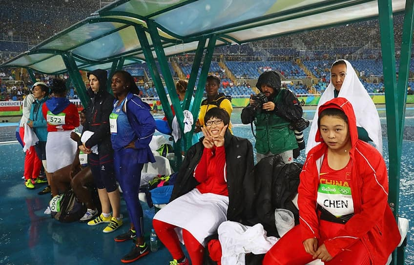 Athletes wait under an awning in the rain in the Olympic Stadium