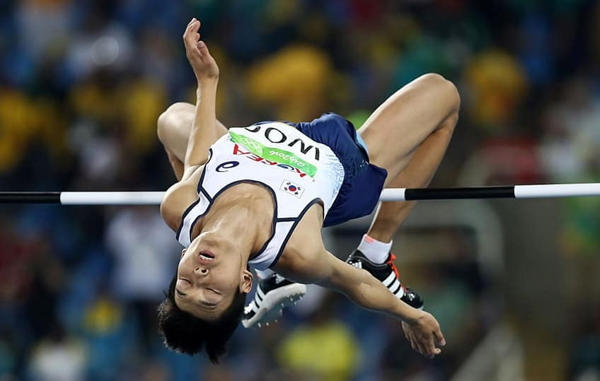 a high jumper looks like he's taking a nap in mid air