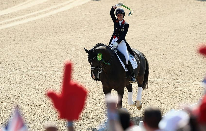 A big foam finger can be seen in the foreground rooting for Equestrian Charlotte Dujardin as she wins gold