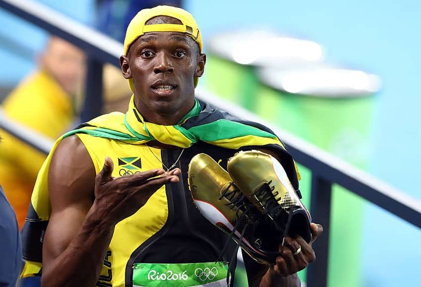 Usain Bolt holds up his golden running shoes