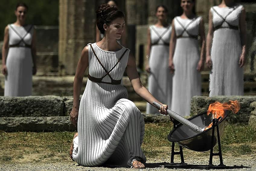 a woman lights the Olympic torch at the Temple of Hera in Olympia