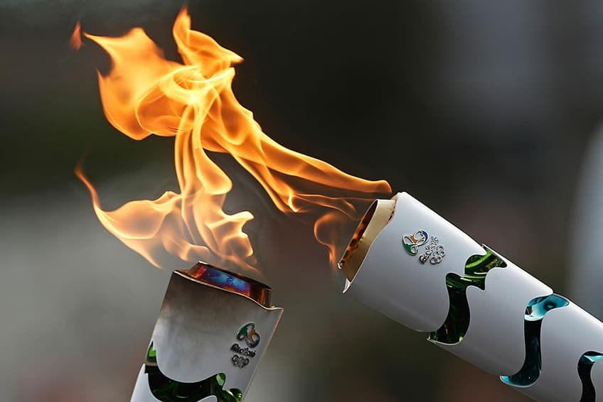 two Olympic torches touching to pass on the flame