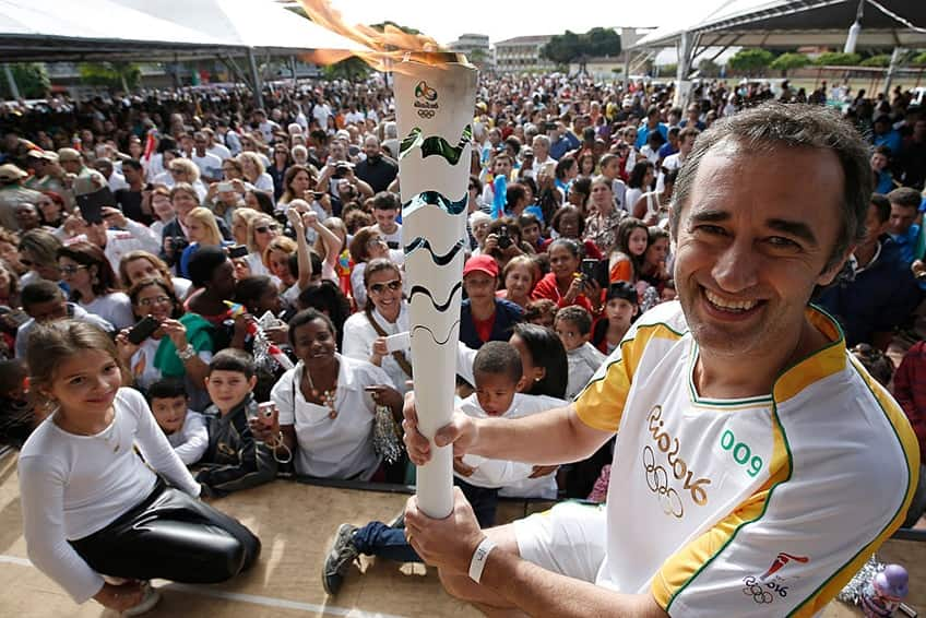 a torchbearer stands in front of a crowd