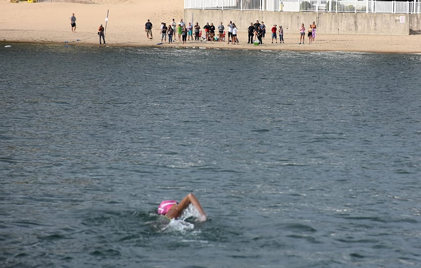Julia is photographed swimming from behind with a cheering crowd on the beach in the distance