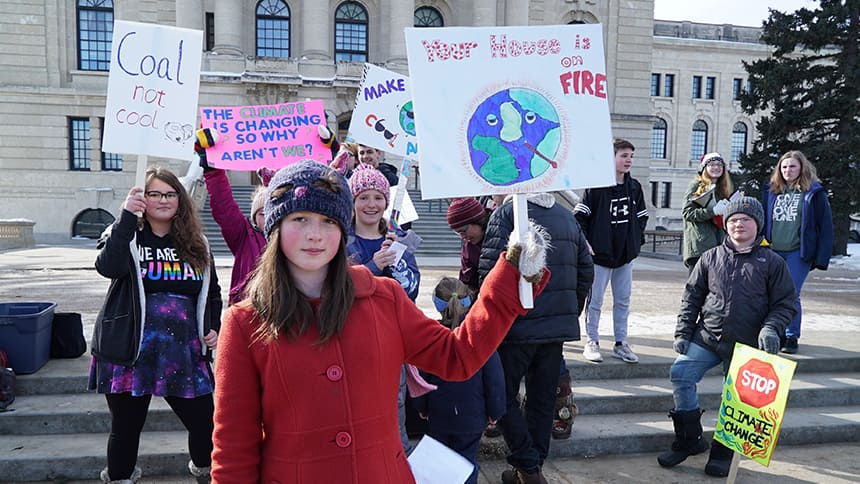 Ada Dechene holds a sign that says Your house is on fire.