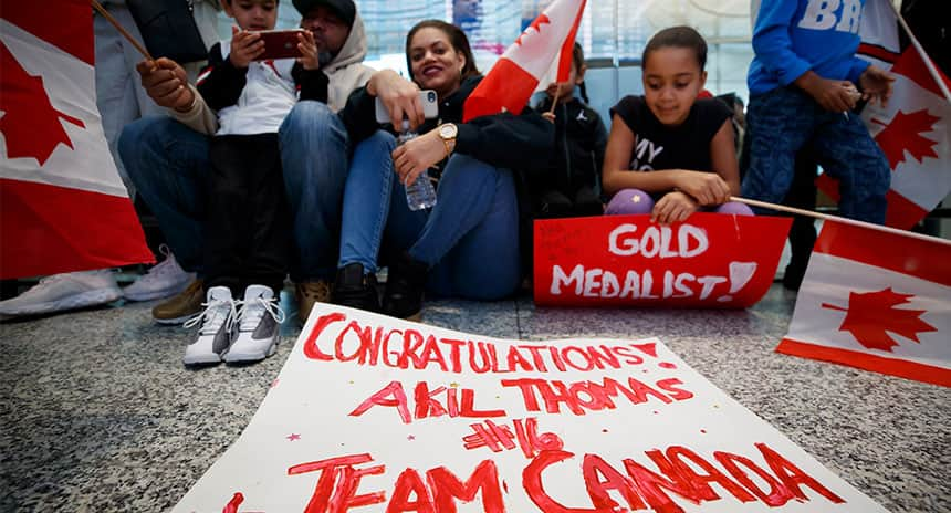 Fans sit in a hockey rink with a sign that reads Congratulations Akil, Team Canada #1