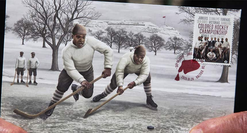 A stamp with an old image of black people playing hockey outside.