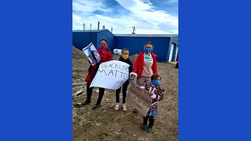 Girls in masks hold Black Lives Matter signs.