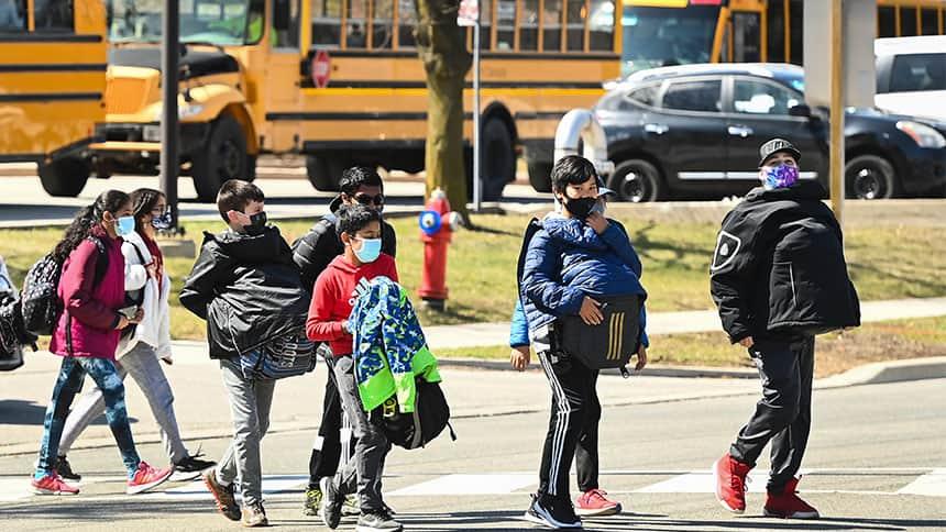 Kids wearing masks cross the street in front of school buses.
