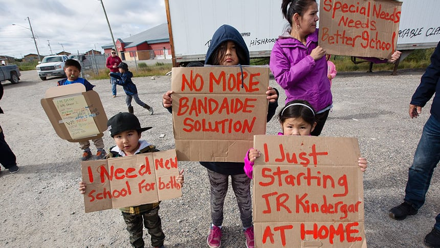 Kids stand with cardboard signs with red writing. One says