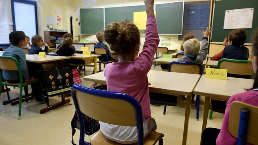 A kid raising her hand in a classroom.