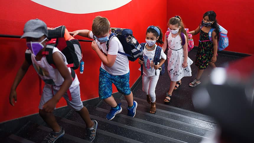 Kids wearing masks walk up a staircase.