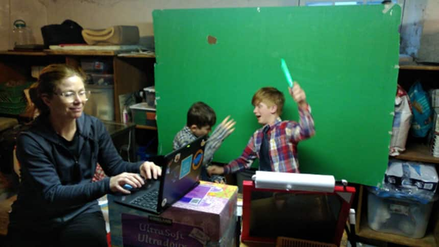 Garnet and Keagan play in front of a green screen.
