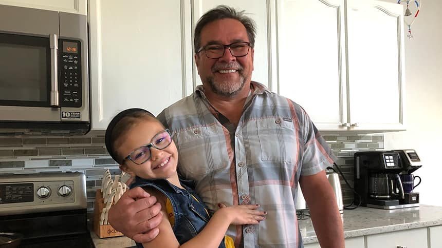 A girl hugs her grandfather in a kitchen.