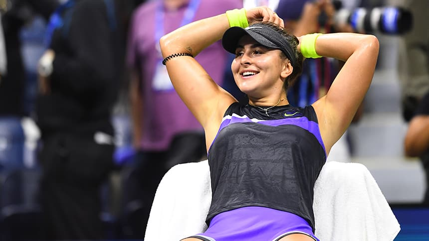 A tennis player sits beside the court, resting and smiling.