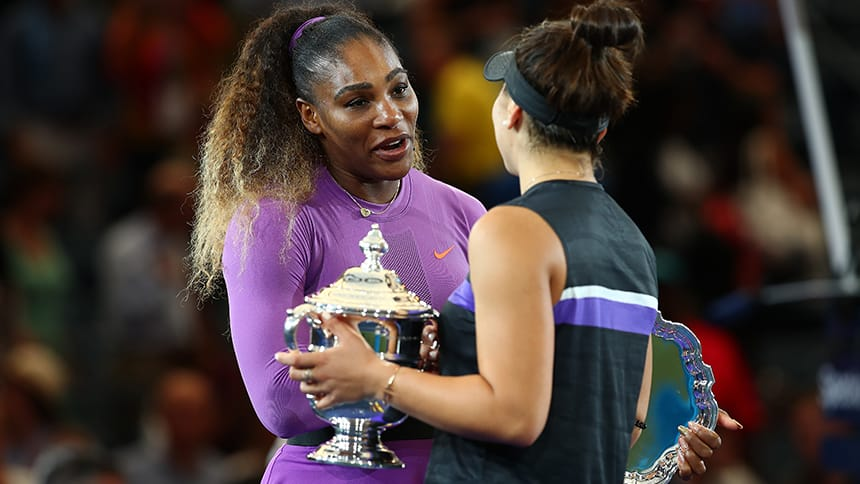 A woman congratulates another woman holding a trophy.