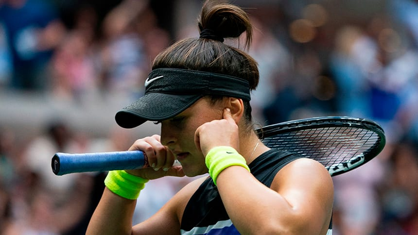 A tennis player blocks her ears with her hands.