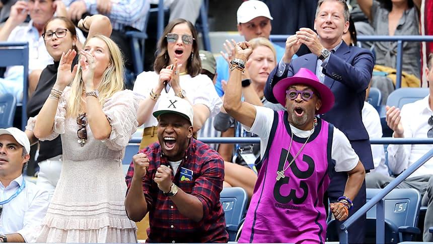 Three woman applaud a tennis match.