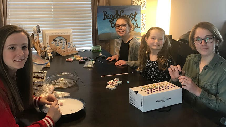 Four girls sit around a table with materials to make earrings.