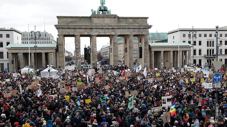 A huge crowd of people in front of a monument in Berlin.