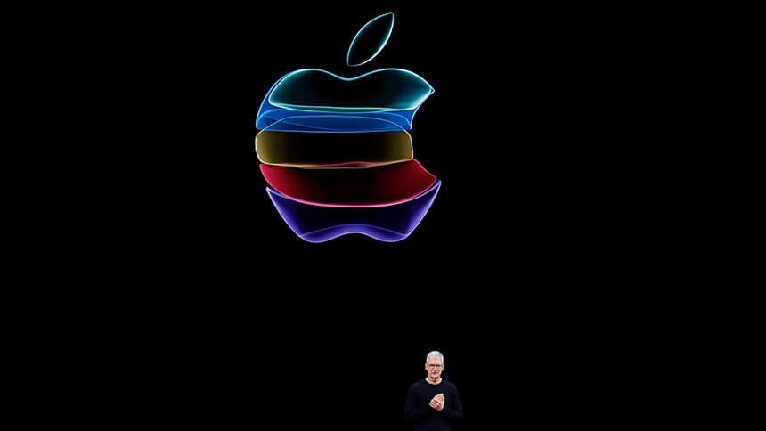 Apple CEO Tim Cook stands below huge Apple logo.
