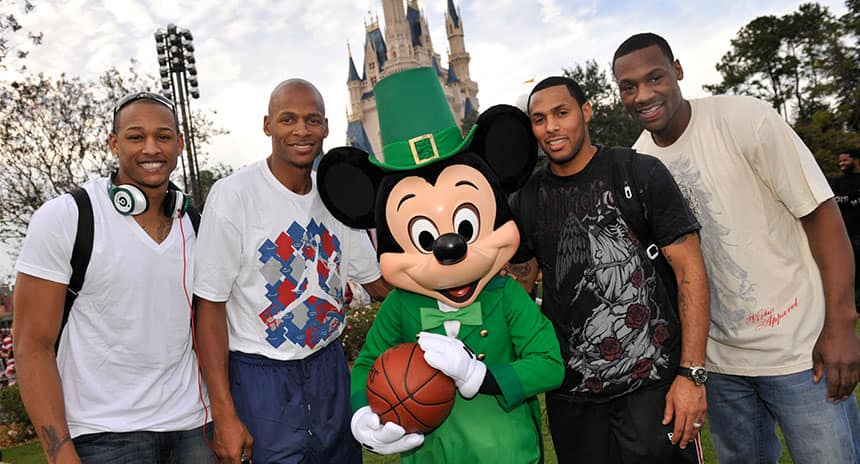 Four athletes pose with Mickey Mouse.