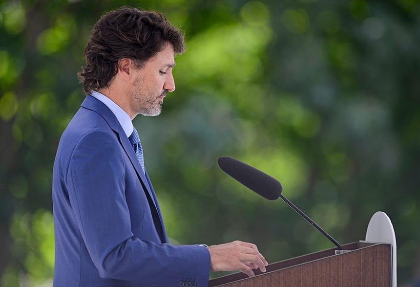 Justin Trudeau at a podium, apologizing publicy.