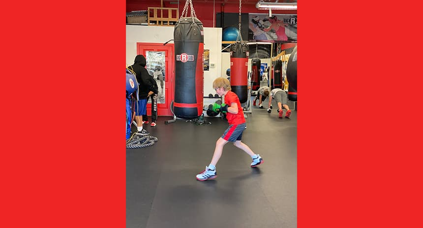 Clark Webster, 12, punching a punching bag during his boxing class.